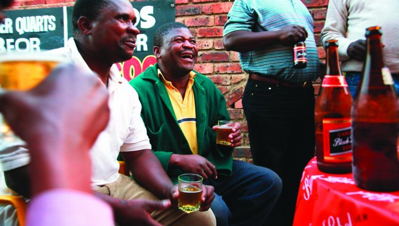 Locals enjoy sharing beer at a tavern in Alexandra township.