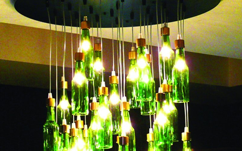 Amstel bottle chandeliers were created as feature lighting, but had the labels removed to be more subtle with the branding.