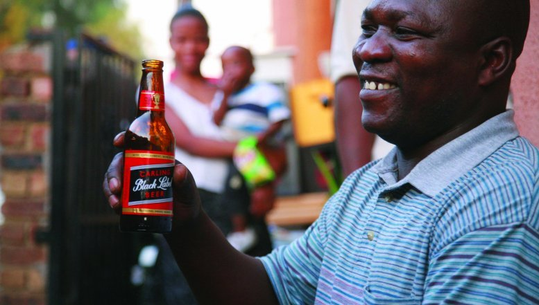 A man enjoying a beer in Alexandra township.