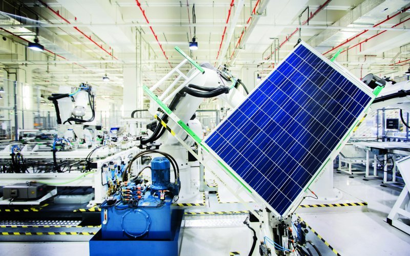 A robot handles a solar panel on the module production line at the REC Solar ASA manufacturing facility in Singapore