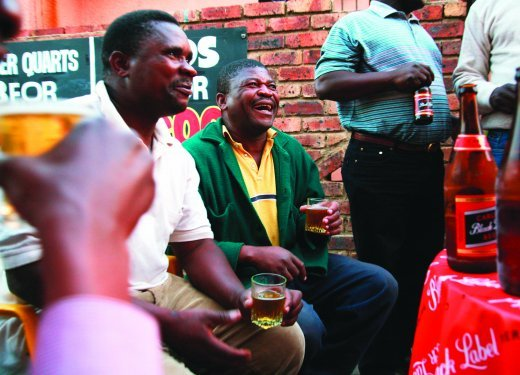 Locals enjoy sharing beer at a tavern in Alexandra township. Image By Philip Meech, One Red Eye..jpg