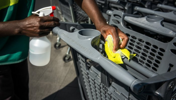 A worker sprays sanitiser on the handle of a shopping cart outside a Pick n Pay supermarket in Johannesburg.
